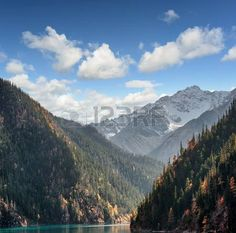 Fantastic view of snow-capped mountains on blue sky background. Snowy peaks, wooded mountains and the Long Lake in Jiuzhaigou nature reserve (Jiuzhai Valley National Park), China. Beautiful landscape. photo