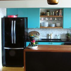 vintage inspired modern kitchen makeover with turquoise cupboards and open shelving, butcher block waterfall island and black appliances.