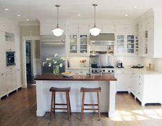White kitchen with bead board, subway tile, butcher block island...