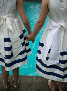 Flower girl dresses in white with navy and white nautical cabana stripes on lower skirt, round white pearl buttons and big white ties in back, Coren Moore Real Weddings