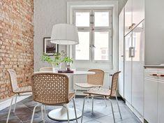 Czerwona cegła na ścianie,białe lakierowane szafki i plecione bambusowe krzesła w aranzacji skandynawskiej kuchni (25262)