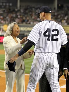 NEW YORK, NY - APRIL 15: Rachel Robinson, wife of Jackie Robinson, welcomes Derek Jeter of the New York Yankees to an on field ceremony prior to their game against the Los Angeles Angels of Anaheim at Yankee Stadium on April 15, 2012 in the Bronx borough of New York City. In honor of Jackie Robinson Day, all players across Major League Baseball will wear number 42. (Photo by Nick Laham/Getty Images)