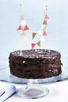 En høj chokoladelagkage med mange lag ser altid festligt ud på fødselsdagsbordet - og så smager den fortrinligt. Pynt den gerne med papirsflag på pinde. De kan købes færdige, men kan også nemt laves selv!