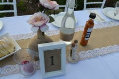 Twine and lace bottles, vases with flowers and sand, framed table numbers all on lace and burlap table runner.