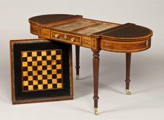 *A Regency Mahogany Games Table Attributable to Gillows of Lancaster. The table of good colour and patination. Having a leather lined top with rounded ends, each opening to allow for storage of chess or backgammon pieces. The centre with a reversible top with a chess board to one side and leather lined writing surface to the other. Supported on four turned tapering legs terminating in brass castors. English, Circa 1810