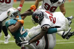 Miami Dolphins running back Reggie Bush is tackled by Houston Texans Johnathan Joseph and Danieal Manning in the first half of their NFL football game in Houston