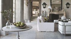 Dans un bel esprit de collection, le grand salon regroupe, autour d'une cheminée en pierre de style Louis XV, des canapés en lin, Caravane, une paire de fauteuils en cuir Le Corbusier chez RBC et un lampadaire Serge Mouille. Près des baies vitrées, une table-guéridon ancienne au plateau de marbre se prête aux natures mortes de l'hiver