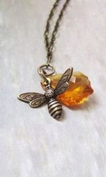 Cute little honey charm & Swarovski crystal charm in amber finish this necklace that depicts the work of a bee. This is a one of a kind design that you will definitely love,  necklace is kept short measuring about 23'' so the charms fall just below the neck.