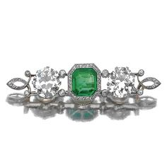 EMERALD AND DIAMOND BROOCH/RING/NECKLACE. The bar brooch centring on a step-cut emerald bordered by millegrain set single-cut diamonds, flanked by circular-cut stones, the three principal stones can be unscrewed, the emerald to be set into a ring, size 53½, the two diamonds onto a bow necklace of négligé design, length approximately 380mm.