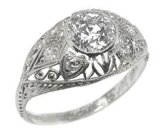 A lovely platinum diamond engagement ring from the Edwardian era. The ring is set with an old European cut diamond in the center that weighs 1.09ct and is EGL certified. The center stone is accentuated by round cut diamonds that weigh approximately 0.20ct. The ring features gorgeous open work, milgrain design as well as lovely engravings. The ring is size 7 1/2, but can be resized. The UGS replacement value of the center stone alone is $7,950  $5,500
