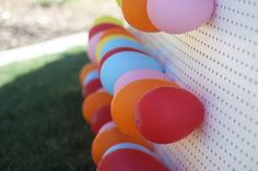Stick balloons through a pegboard and see who can pop the most by throwing darts