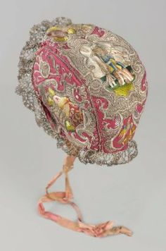 Infant's bonnet 1650–1725 French or Italian | Polychrome silk and silver yarns embroidered on red silk ground, trimmed with silver lace. Vegetative design: baskets with pears on sides; top: cartouches framing fruit, scene of Tobias and angel, and bird at base. Lined with polychrome silk; pink silk ties. | Dimensions: 11 cm (4 5/16 in.); Legacy dimension: 4 1/2 x 3 1/2 in. Medium: Silk and silver yarns embroidered on silk; silver lace trim | Accession Number: 38.1323