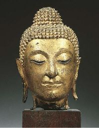 a thai, ayutthaya style, gilt-bronze head of buddha shakyamuni 17th/18th century His face with serene expression, incised eyes below arched eyebrows, aquiline nose, smiling lips, elongated earlobes, curled hairdress and usnisha 30 cm high, mounted