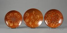 Three Large Redware Slip-decorated Plates, America, early 19th century, round plates with coggled rims, (glaze wear, chips), dia. 11 1/4, 11 7/8, 12 1/2 in.    Sold for $ 1,778