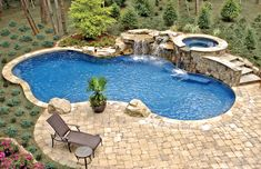 Free form swimming pool with elevated spa and rock waterfall
