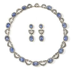 A Rare Sapphire and Diamond Necklace by Carl Fabergé formed of thirteen graduating clusters of blue sapphires encircled by rose cut diamonds, joined by diamond set bows suspending floral swags, supported on openwork galleries, set in silver and mounted on gold (later matching earrings). By Fabergés Chief Jeweller: Albert Holmström St Petersburg, 1908