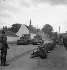 Cromwell and Stuart tanks of Guards Armoured Division passing German POWs being guarded by paras during the advance to Brussels, 3 September 1944.