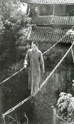 :::::::::: Vintage Photograph ::::::::::  This photograph scares me and yet at the same time I am in awe of the single purpose and focus one must have had to walk across this bridge.  The Jiangyou Figure Hill Temple. Simple iron chain bridge, China, 1930s
