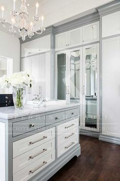 White and gray closet features a gray cabinets fitted with white cabinet doors adorned with polished nickel pulls and knobs.