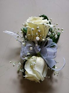 White roses, baby's breath and green leaves with silver trim on a wristlet Wrist Corsage, Baby's Breath, Corsages, Boutonnieres, White Roses, Green Leaves, Floral Wreath, Wreaths, Silver