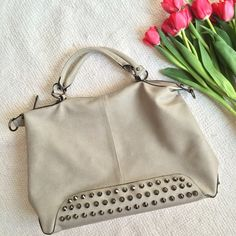 """Vegan Grey Studded Handbag OFFERS WELCOME. PLEASE USE THE OFFER BUTTON. I do not negotiate price in the comments. Sophisticated with an edge. Light grey, studded handbag. Few blemishes noted in the photos above. Otherwise in really good condition. Inside in excellent condition. Has a zip middle compartment and pockets for cell phone. Zip pocket in back. Studs are dull, not spiky. Zip to close. Faux leather. Length is 12"""". Width is 17"""". Depth is 5"""". Handle drop is 5"""". I am modeling the black…"""