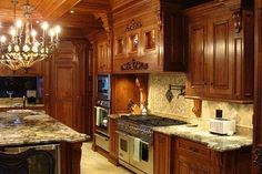 Regal looking kitchen with custom cabinets in knotty cherry with moulding, columns, hand carved corbels and accents and a stained, glazed and rubbed finish. My all time FAVORITE Kitchen!!!!!!!!!