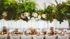 The reception marquee featured timber beams trailing a mass of green foliage, studded with proteas — a flower native to Cheree's home in South Africa. Photograph courtesy of Jonas Peterson.