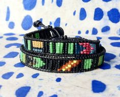 """- 14""""L  - .8""""W  - seed beads  - black leather cord   - adjustable button clasp"""