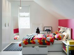 Ein weißes und rosafarbenes Schlafzimmer mit MALM Bettgestell hoch mit 4 Schubladen in Weiß und TOFSVIVA Bettwäsche-Sets in Bunt