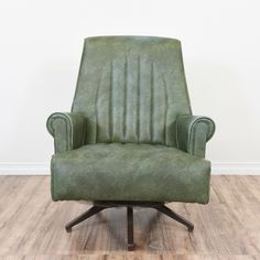 This mid century modern swivel armchair is upholstered in a durable distressed dark sage green vinyl. This retro car seat style chair is in great condition with a swivel base, tall back and channel stitching. Unique and comfortable chair! #midcenturymodern #chairs #armchair #sandiegovintage #vintagefurniture