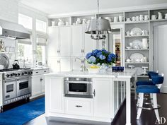 Marble subway tiles are used for the backsplash of a Beverly Hills kitchen. Open shelves display an assortment of ceramic pitchers and serving pieces.