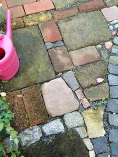 mis-matched pavers, bricks, stones make a mosaic-like patio. I like the patina of moss.