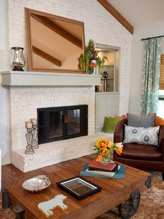 As seen on HGTV's Property Brothers, the focal point of this bright yet cozy living room is a brick fireplace with a white faux finish. The wood-and-metal coffee table and acacia wood flooring balance the more feminine, floral window treatments. Jonathan and Drew had the rose-colored mirror (a family heirloom of the homeowners) custom framed for the mantel.