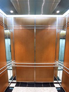 This elevator interior installed at 60 Columbia Way modernized the wood veneer cab with bold stainless steel inlay bars and mirrored interior corners subsequently making the space look bigger and brighter.