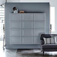 Graue METOD Wandschränke an einer grauen Wand, davor ein Sofa.