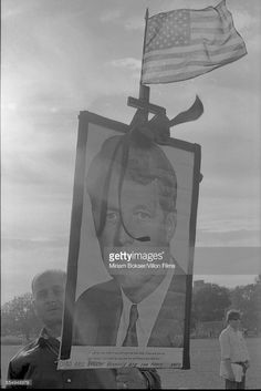 A man holds up a photo of Robert F Kennedy while protesting during the Democratic National Convention, Chicago, Illinois, 1968. The sign reads 'God and Robert Kennedy are for peace Amen' and has an American flag affixed to it.