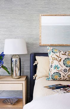 Conjure your personal oasis with cool hues and subtle details. Ocean colors, like this textured blue sea grass wallpaper, create a calming space. Click through for more bedroom ideas for decorating your home.