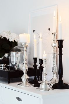 Plethora of silver and black candles make a beautiful arrangement for any occasion or just to add drama and glamour to a room.