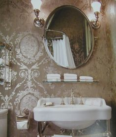 This elegant bath has beautiful wallpaper in a french classical pattern in metallic on taupe
