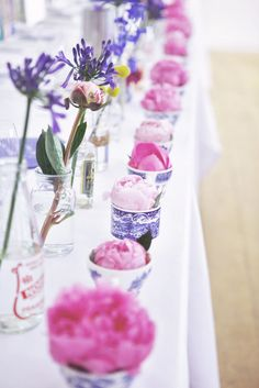Pink peonies add a splash of colour to this blue and white china themed wedding reception tablescape.