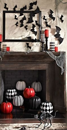 Vampire Red, Black and White Halloween Mantel Ideas | Digs Digs - a stylish mantel with bats and red and checked candles and a fireplace filled with checked, striped and red pumpkins