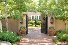 Artistic Integrity - Colorado Homes and Lifestyles - Built in 1989, the 6,200 square-foot ranch house is true to New Mexico Territorial Revival style. Wooden gates open onto a charming courtyard garden featuring meandering flagstone paths and a cast-iron fountain.