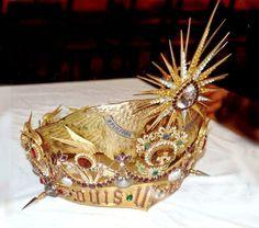 """Couronne de Saint Michel qui se trouve à la maison du Pelerin au Mont Saint Michel. Cette Couronne est en laiton doré. Sur cette couronne se trouvent des Topazes, des Diamants des Améthystes, Rubis, Aigues Marines. Cette couronne est en forme de visière de casque, ornée de dix coquilles argentées au-dessus d'un bandeau portant le """"Quis ut Deus"""" entre deux pointes. La couronne est en laiton doré. La coquille et les pointes sont en laiton argenté. Signature : Mellerio orfèvre Paris. Date…"""