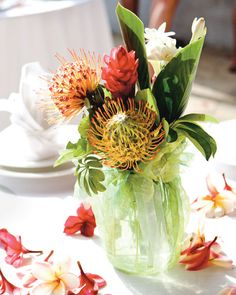 These casual arrangements of pincushion protea, red ginger, and white tuberose…