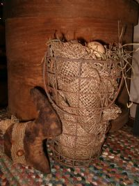 Wouldn't I love to have this egg basket!!  Note the braided runner it's seated on.... they come in different sizes, shapes, colors...and add alot to a grouping!!  The prim bunny is not to be overlooked either!!!