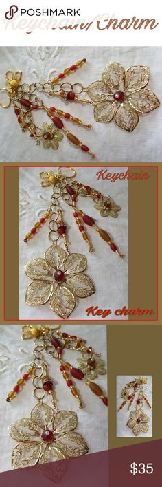 🆕️KEYCHAIN/CHARM HANDCRAFTED GOLD & RED 🆕️ HANDCRAFTED KEYCHAIN/CHARM. DECORATIVE GOLD & RED, 2 GORGEOUS GOLDTONE FLOWERS WITH A GLITZY CENTER.GOLDTONE CHAINS WITH ATTACHED GLASS BEADS IN RED & GOLD, MAKE UP STREAMERS. ALL ATTACHED TO A LARGE GOLDTONE LOBSTER CLAW & A GOLDTONE CIRCLE RING, FOR YOUR KEYS.EACH KEYCHAIN/CHARM IS HANDCRAFTED  WHICH MAKES EACH,  A ONE OF A KIND CREATION.  DECORATE YOUR BAG, COMPUTER CASE OR WHATEVER YOU WISH!!! GIVE AS A GIFT OR TREAT YOURSELF...PLEASE ASK ALL…
