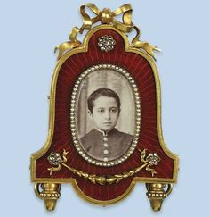 AN ANTIQUE ENAMELLED PHOTO FRAME, BY FABERGÉ   The small bell-shaped frame with orange-red guilloché base centering an oval photo compartment within a halfpearl-set rim, applied with rose-cut diamond rosettes, acorn feet and bow surmount, ivory back, Russian, circa 1900