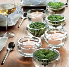 Os crisântemos verdes, intercalados com velas, fazem uma combinação simples e elegante