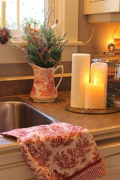 Change flowers in kitchen to evergreens. Love the toile dish towel. Wonder if I could find some in blue or green for my kitchen.