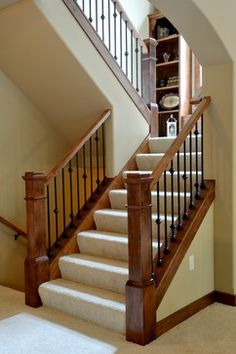 Arts and Crafts or Craftsmen staircase with maple box newel posts, matt black spindles and built in bookcases in landing by Belman Homes in 2012 MBA Parade of Homes The Roycroft #belmanhomes #waukeshabuilder #milwaukeebuilder